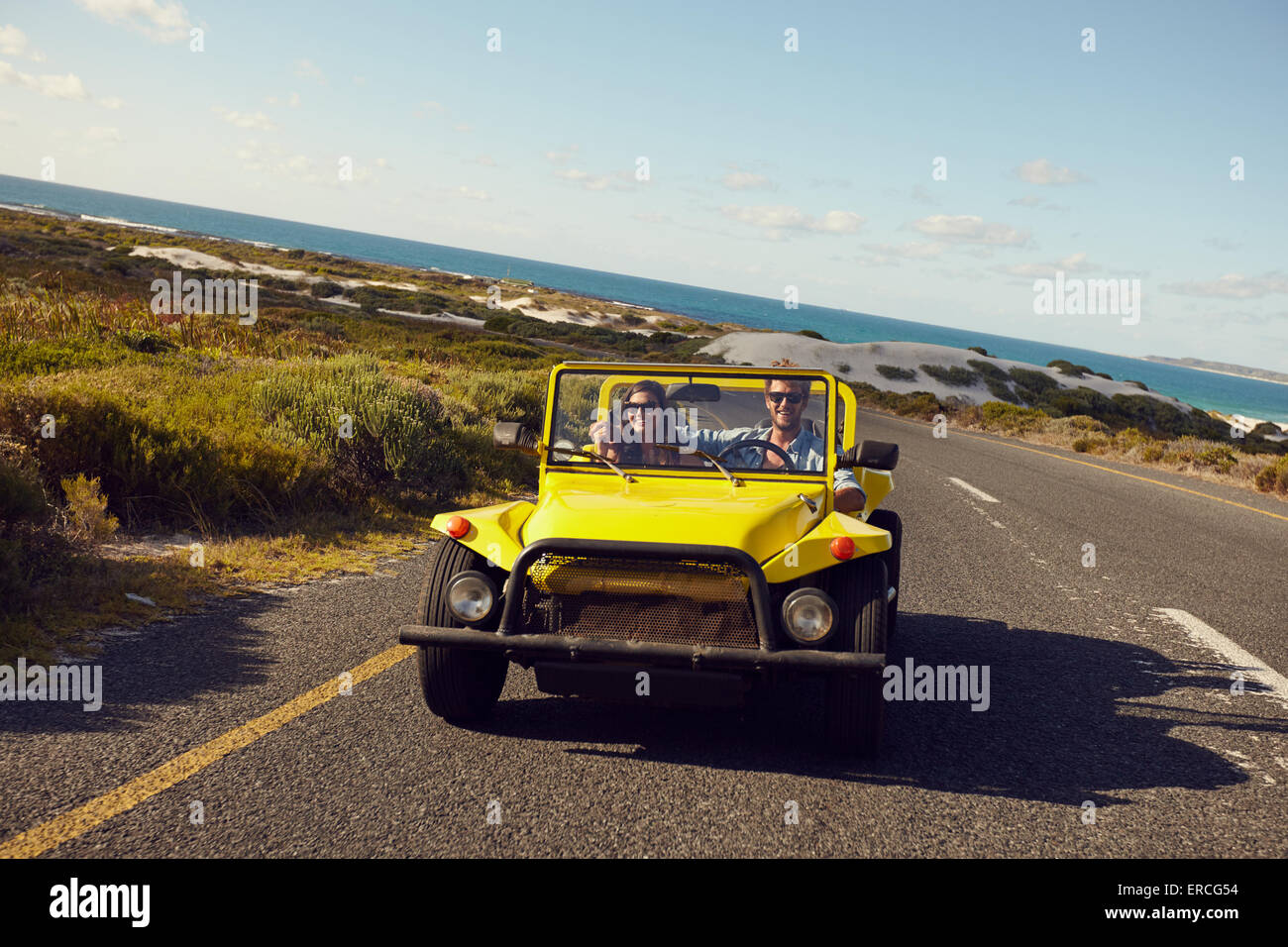Young couple driving in a car on a open road with blue sky and sea in background. Young couple on road trip on summer - Stock Image