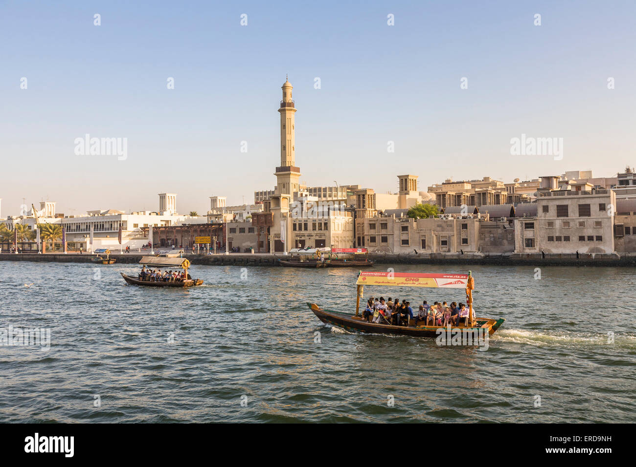 Traditional local passenger ferry across Dubai Creek, from Bur Dubai to Deira, Dubai, UAE, Grand Mosque minaret Stock Photo