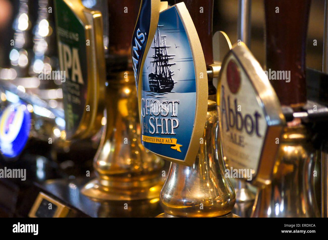 real-ale-handpumps-and-pump-clips-on-a-pub-bar-adnams-ghost-ship-greene-ERDXCA.jpg