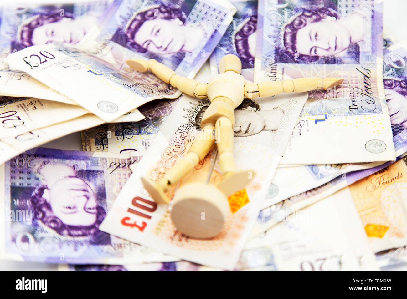Wooden man rolling in money rich wealthy millionaire wealth wealthy millionaires cash pounds notes pound UK british - Stock Image