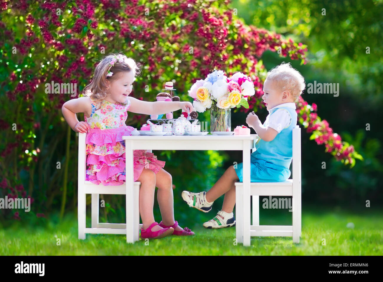 Tea garden party for kids. Child birthday celebration. Little boy and girl play outdoor drinking hot chocolate and - Stock Image