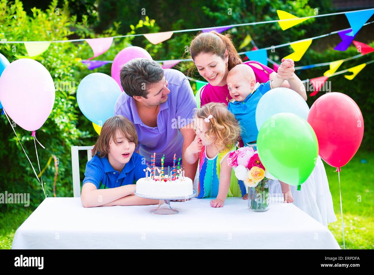 Happy big family with three kids enjoying birthday party with cake blowing candles in garden decorated with balloons - Stock Image