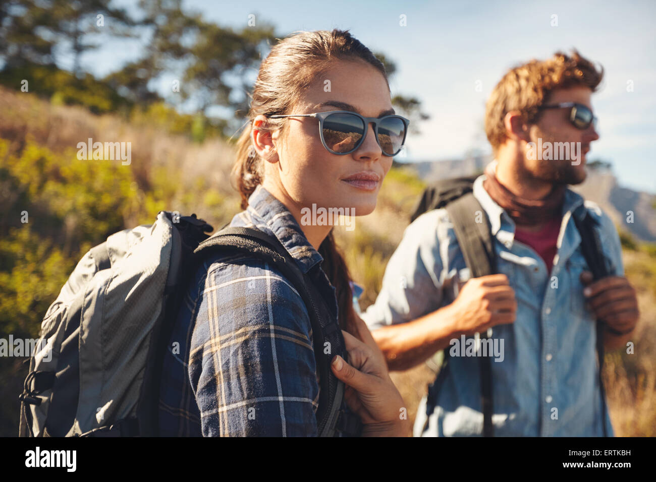Pretty young woman on a hiking trip with man in the background. Caucasian couple on hike in countryside - Stock Image