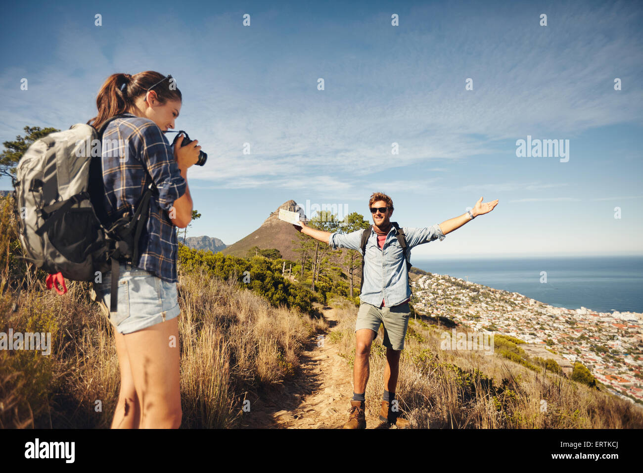 Outdoor shot of young woman photographing her boyfriend in countryside while hiking. Hiker couple enjoying during - Stock Image