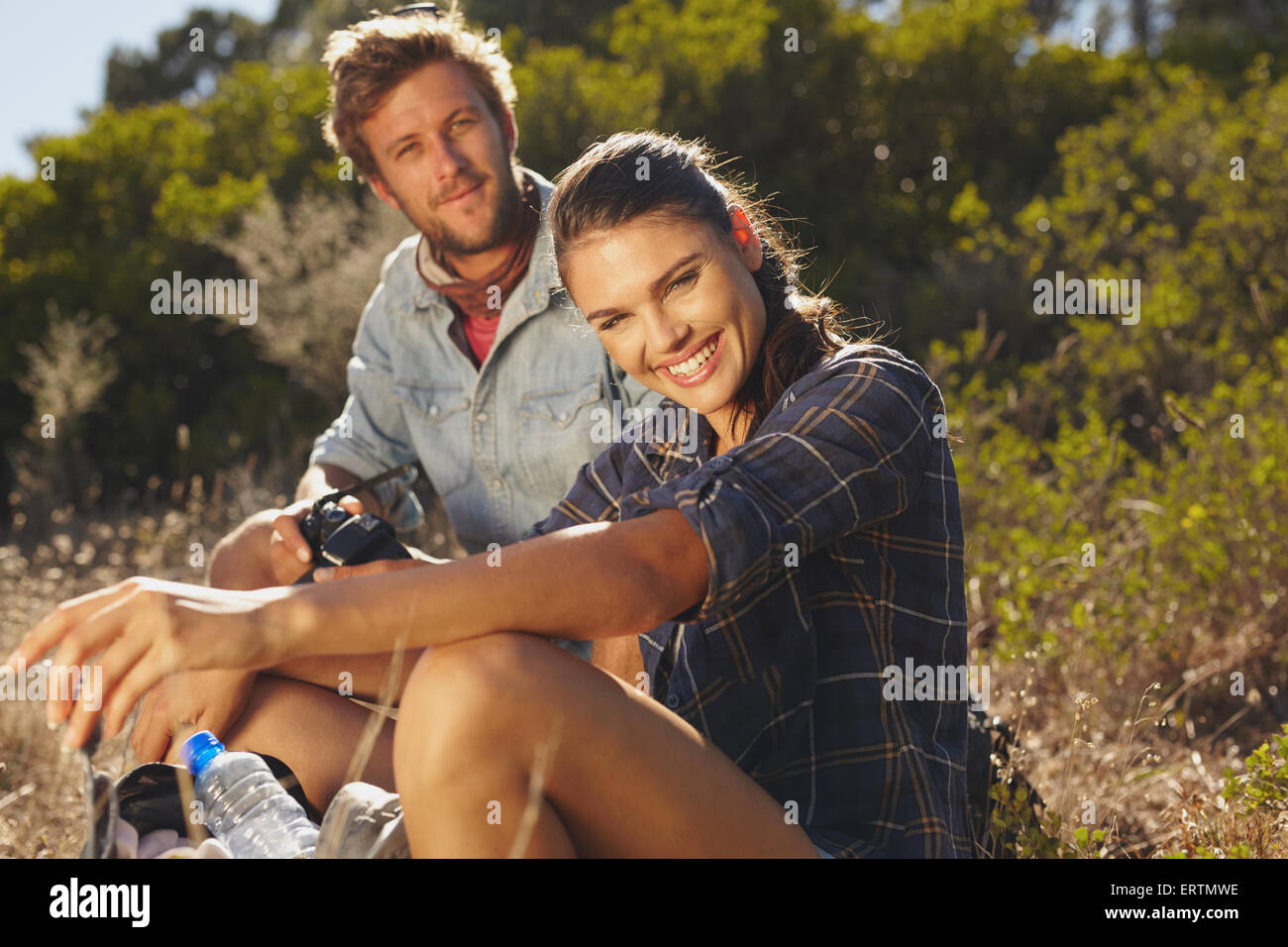 Portrait of happy young woman with her boyfriend taking a break on a hike. Couple hiking on summer vacation, Woman - Stock Image