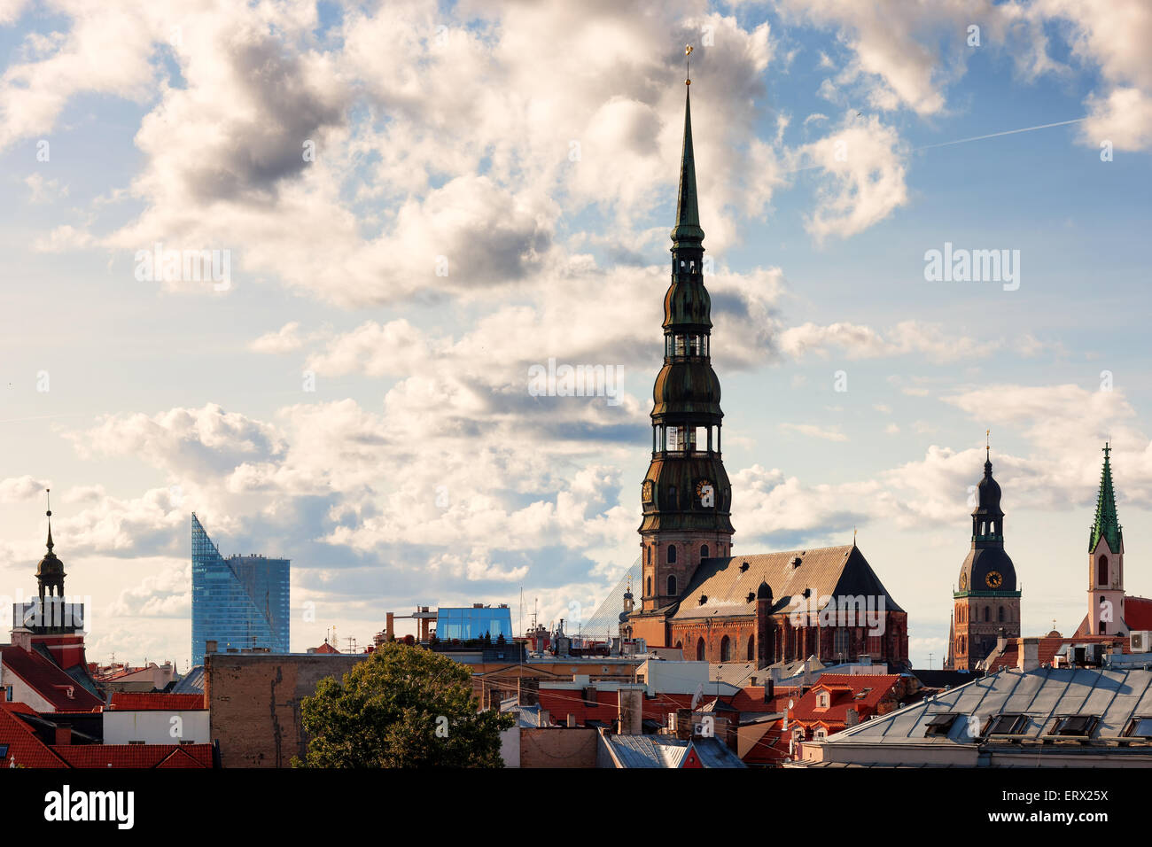 Church spiers and roofs of the old city of Riga in the beautiful sunny summer day with clouds - Stock Image
