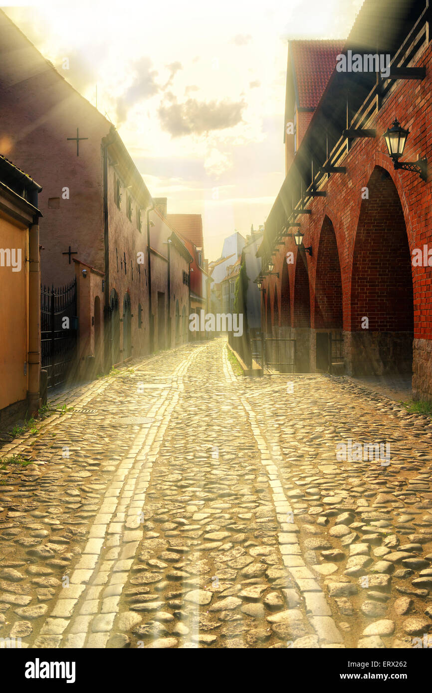 The rays of the sun for about an old fortress wall in the broad street of Riga old bruschatoy. Latvia - Stock Image