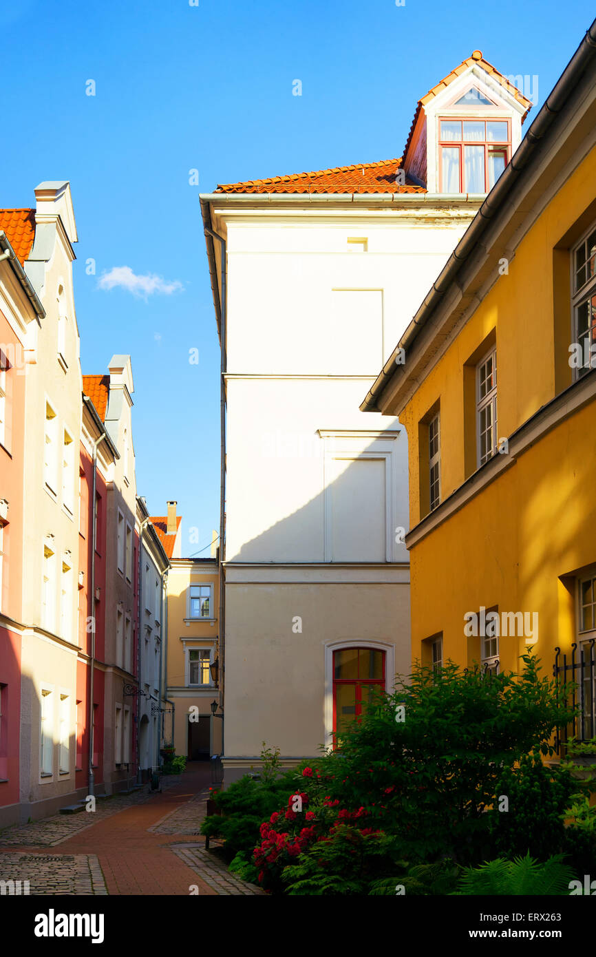 Red walkway with flowers in the garden in the courtyard houses in the old quarter of the city of Riga - Stock Image