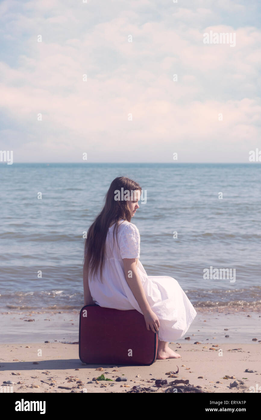a girl is sitting on a red suitcase at the sea - Stock Image