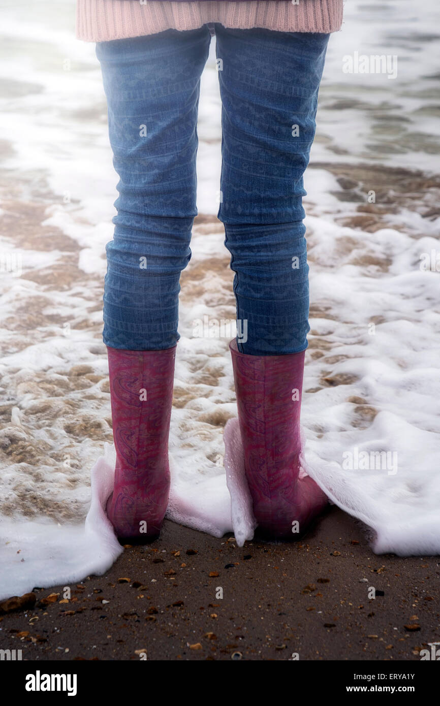 a girl standing with wellies at the beach - Stock Image
