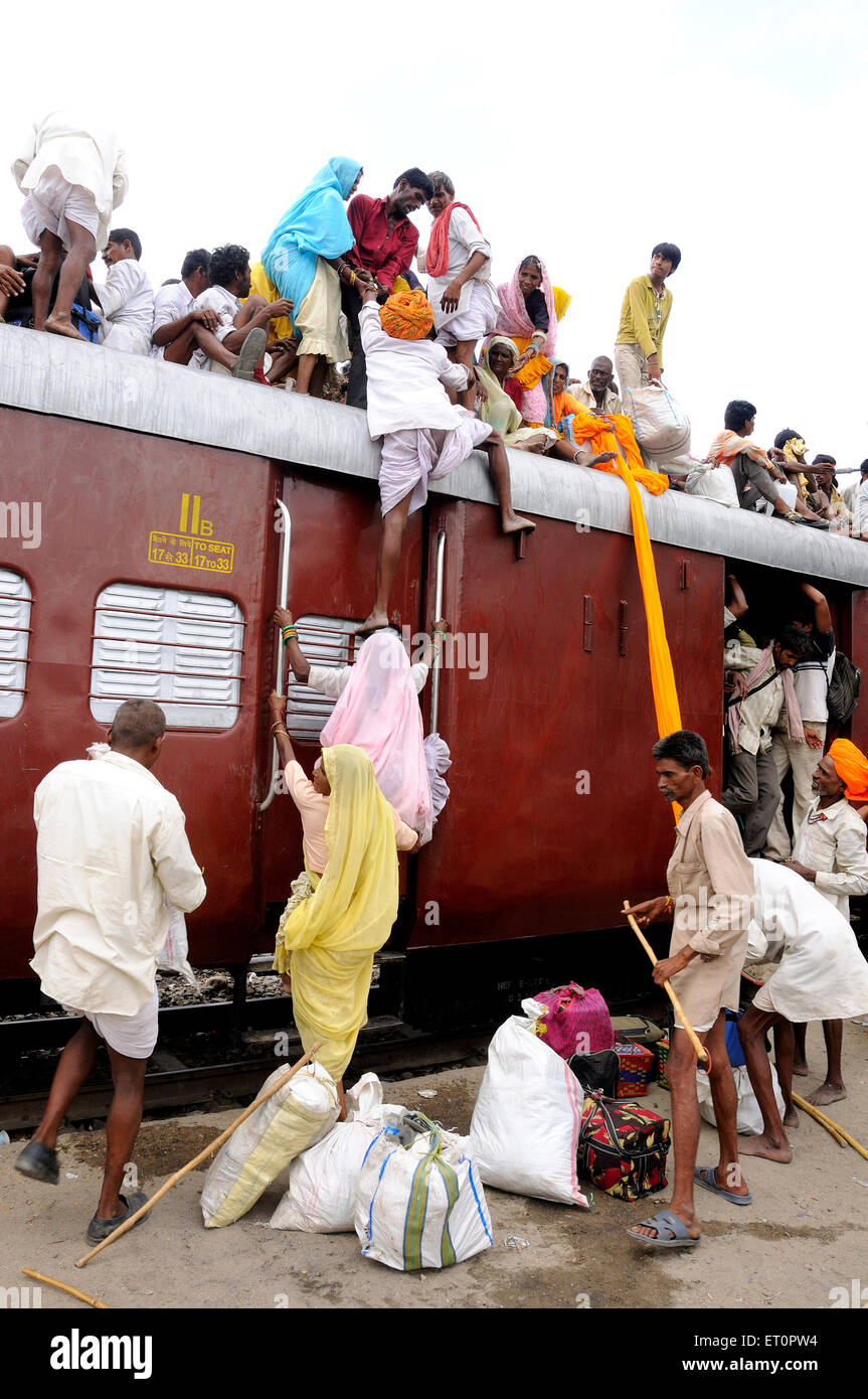 People climbing on roof of train for risky travel ; Marwar railway station ; Rajasthan ; India - msa 155941 - Stock Image