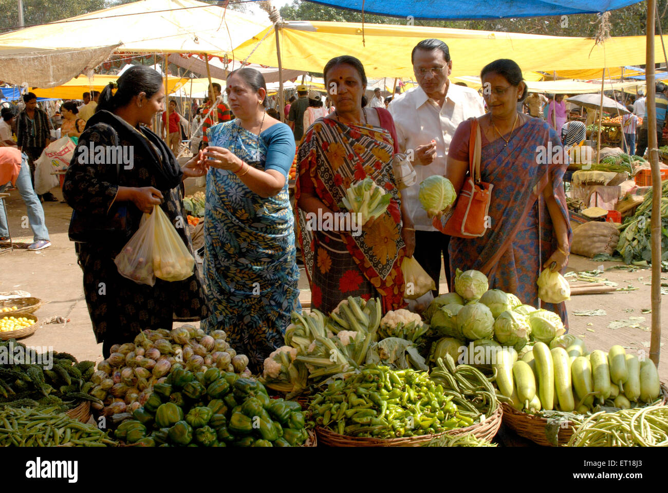 Women purchasing vegetable from market ; Devlali ; Maharashtra ; India MR# 364 - Stock Image