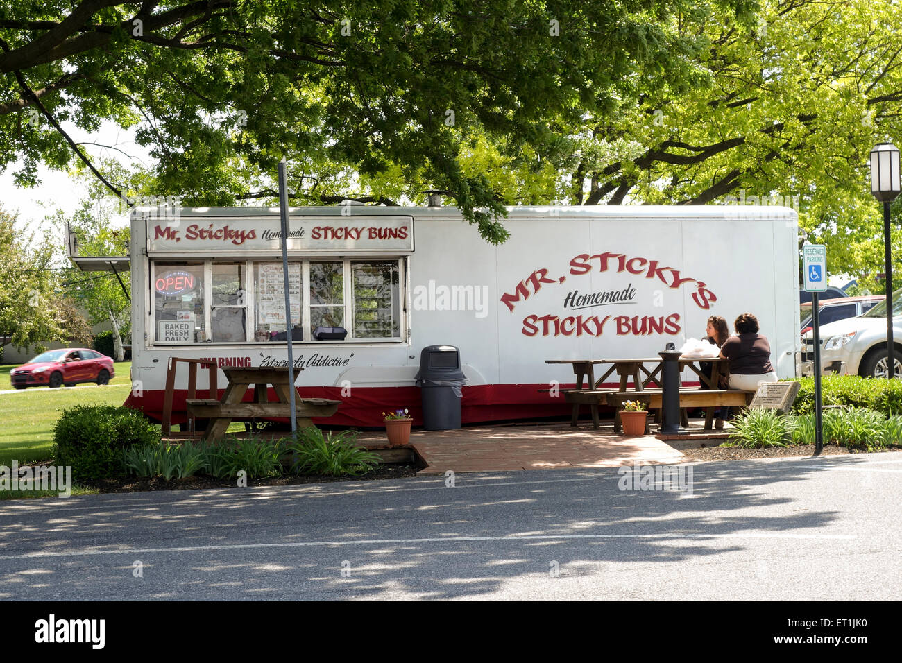 Two people on outdoor terrace at Sticky buns, food truck in Lancaster, Pennsylvania, USA. - Stock Image
