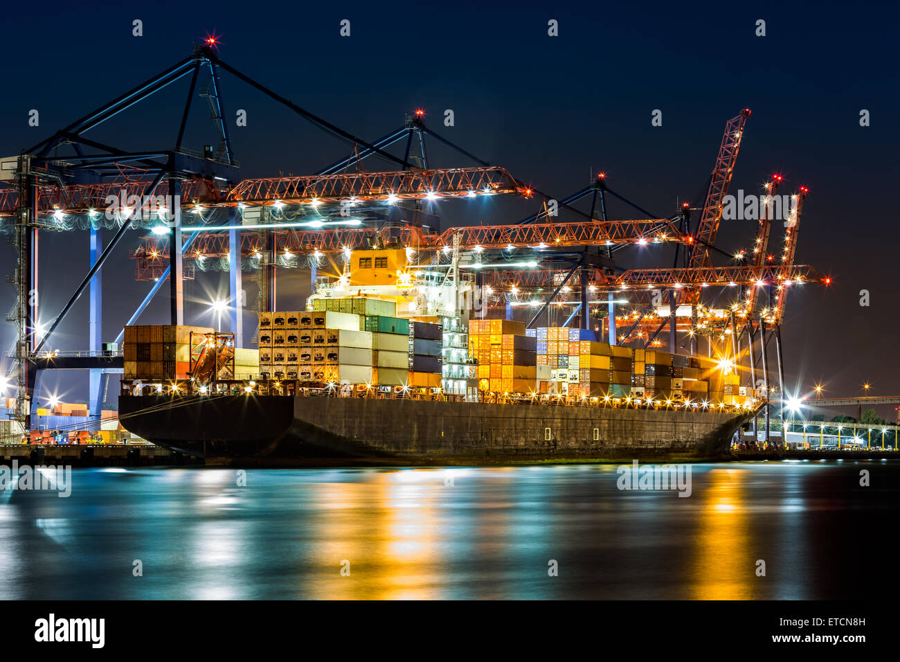 Cargo ship loaded in New York container terminal at night viewed from Elizabeth NJ across Elizabethport reach. - Stock Image