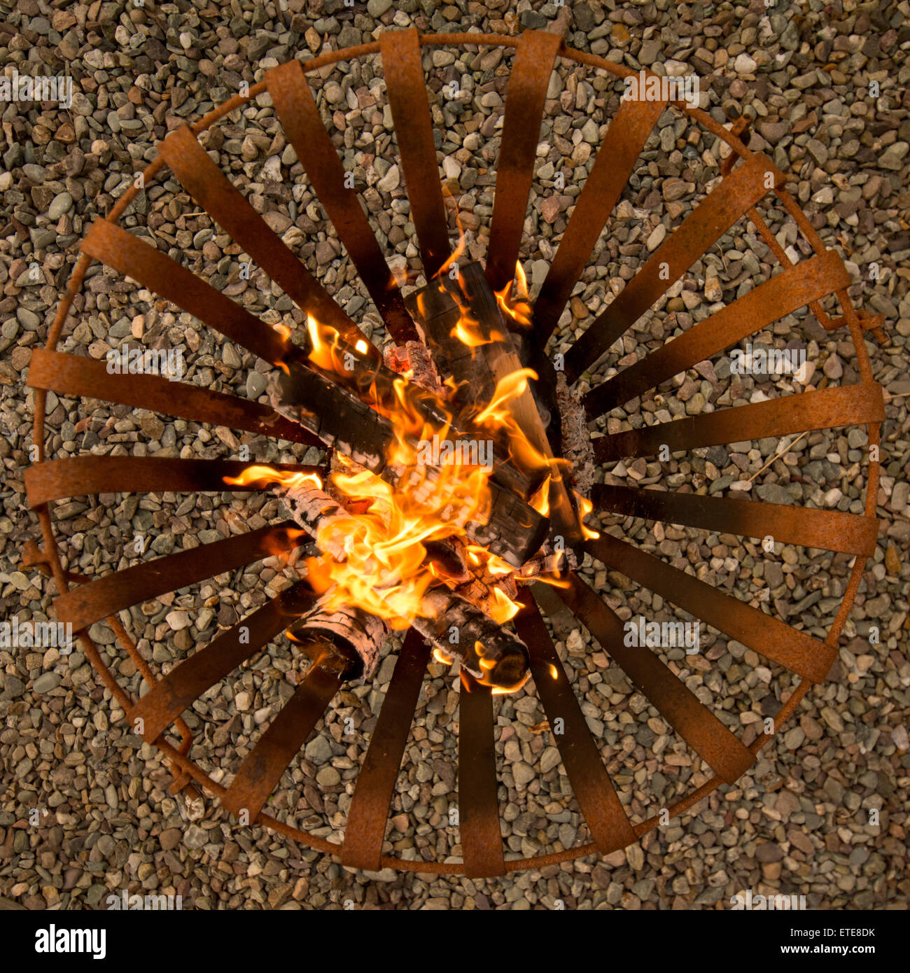 Wood burning in rusted metal brazier on a summers evening - Stock Image