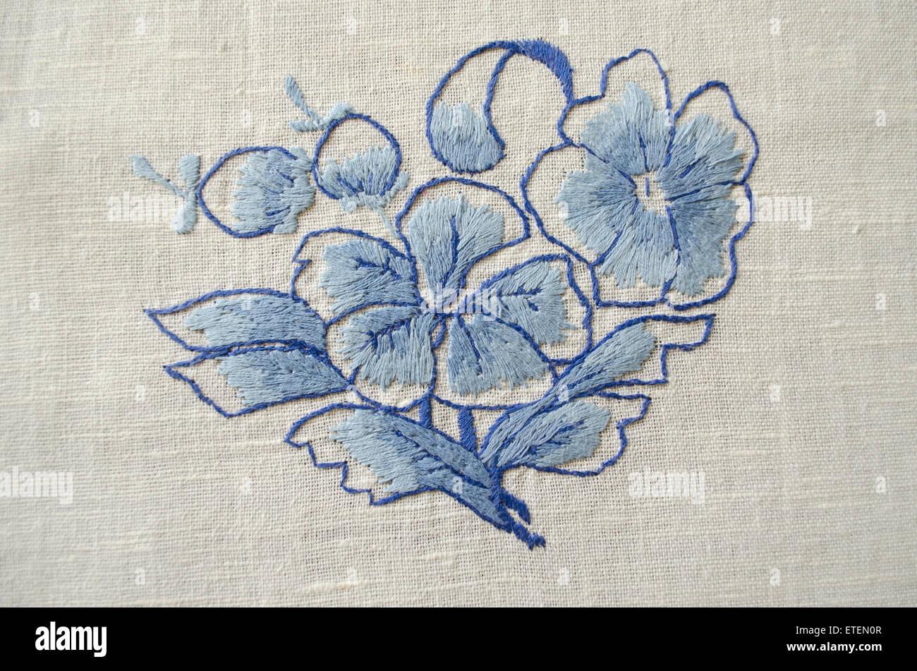 Embroidered satin stitch blue floweron cotton cloth - Stock Image