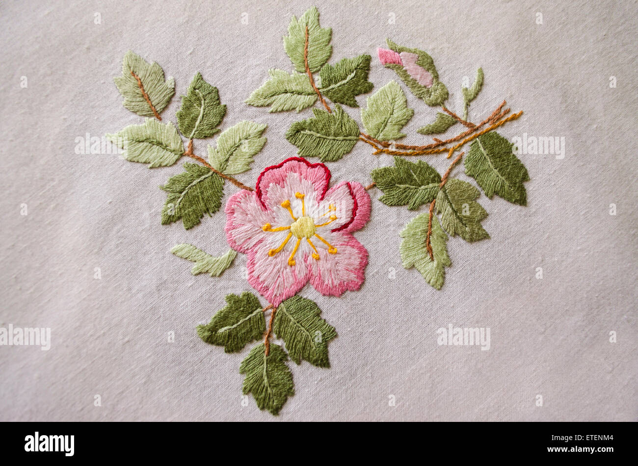 Embroidered satin stitch pink floweron cotton cloth - Stock Image