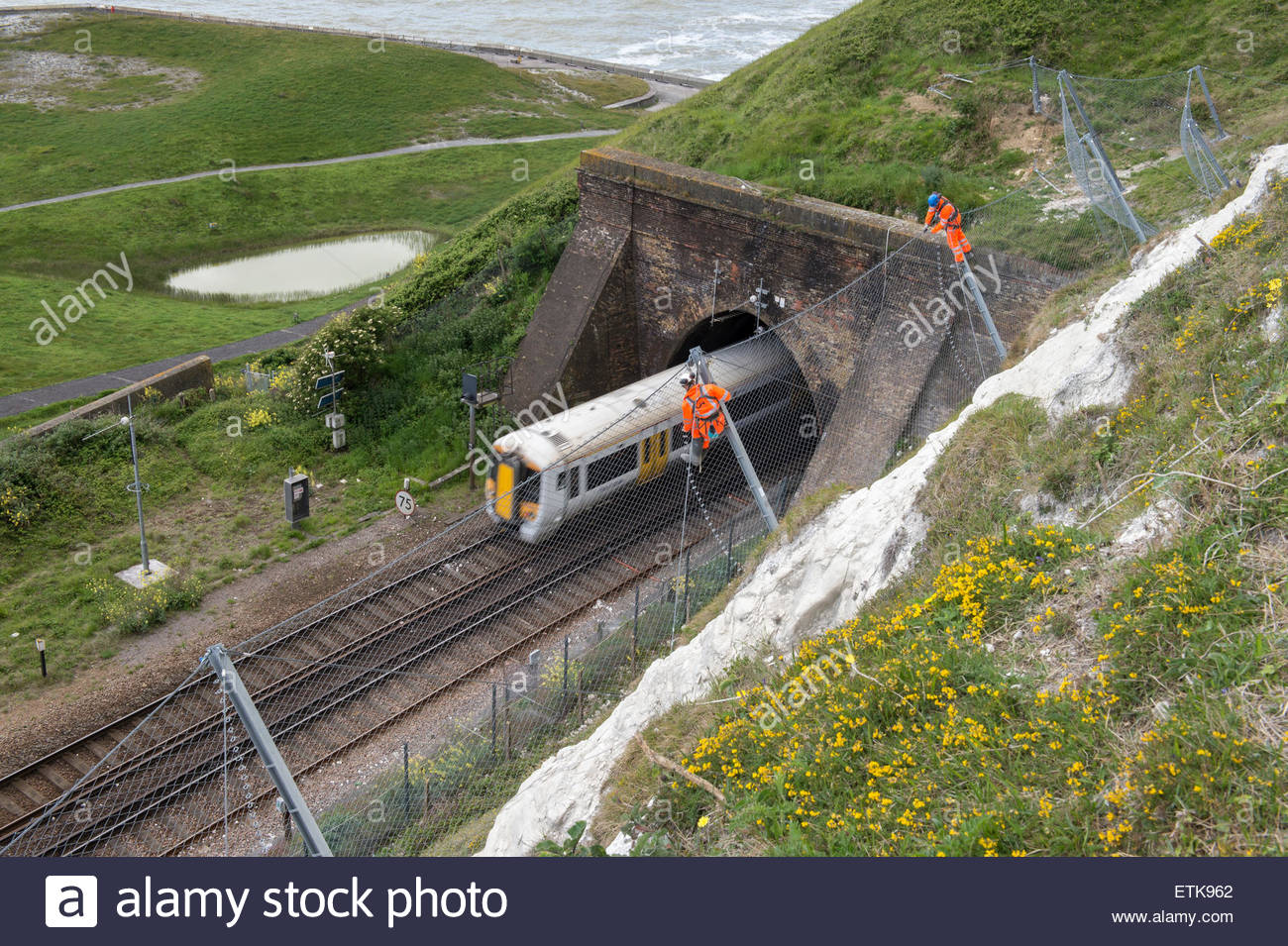 Workers at height constructing catch fence to protect railway below the White Cliffs of Dover - Stock Image