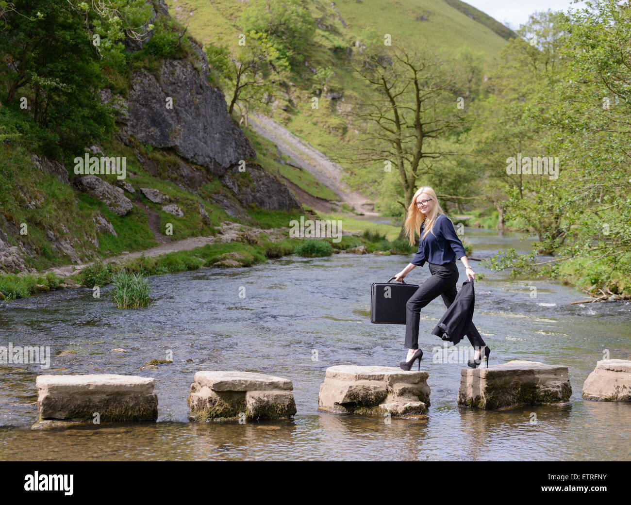 young business woman stepping stones to success metaphor - Stock Image