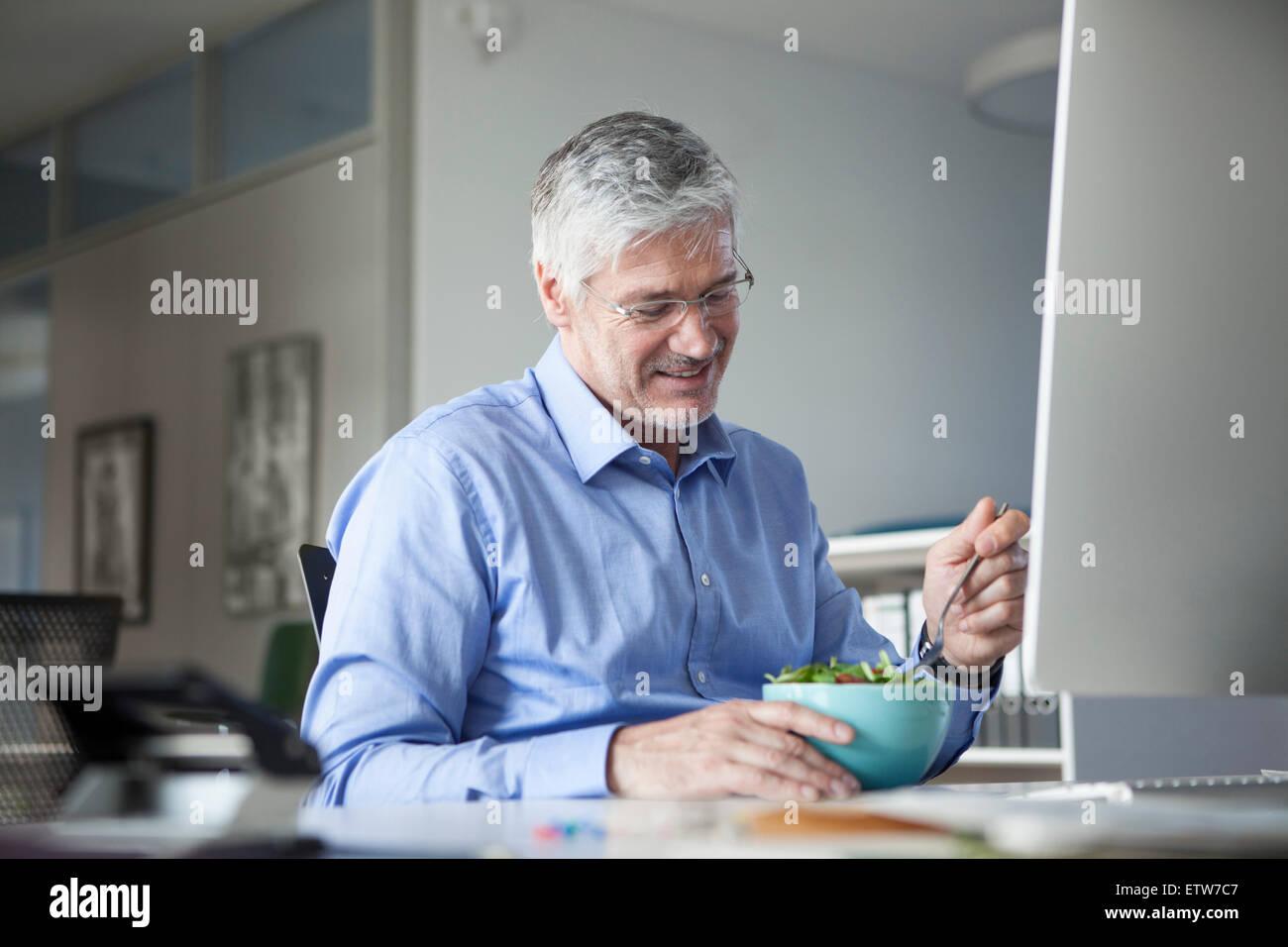 Businessman sitting at desk, eating salad - Stock Image