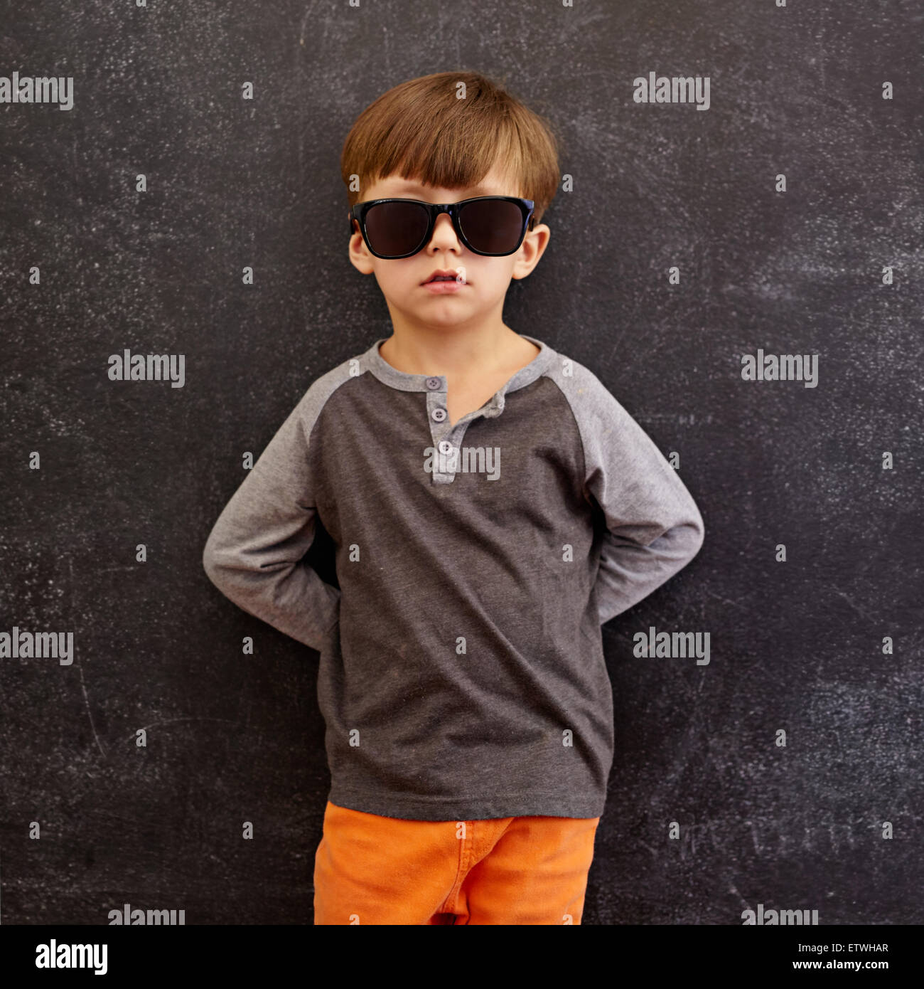 Portrait of innocent little kid wearing sunglasses. Little boy leaning on a blackboard. Square composition. - Stock Image
