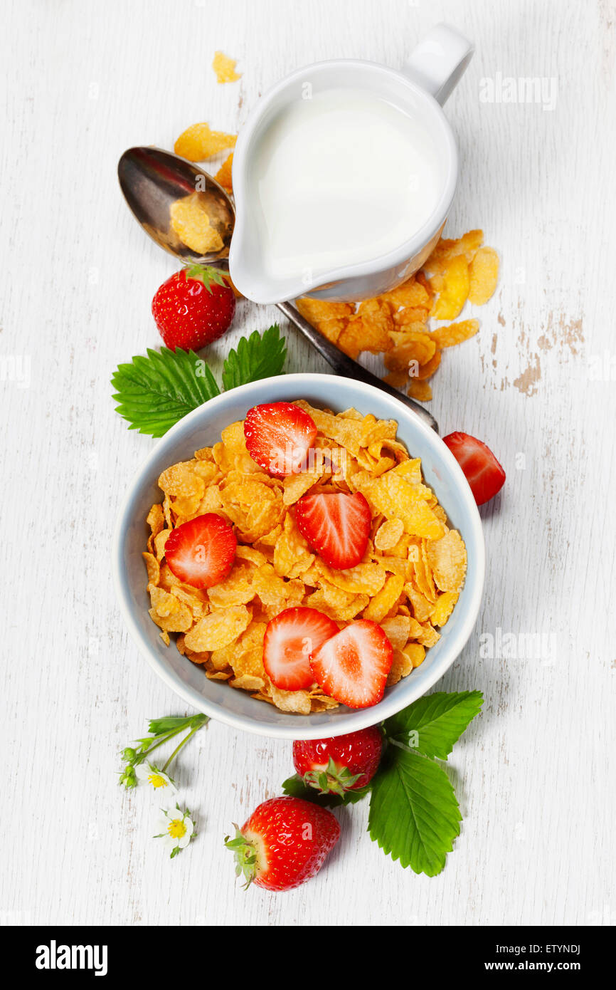 Healthy Breakfast with corn flakes, milk and strawberry on old wooden background. Health and diet concept - Stock Image