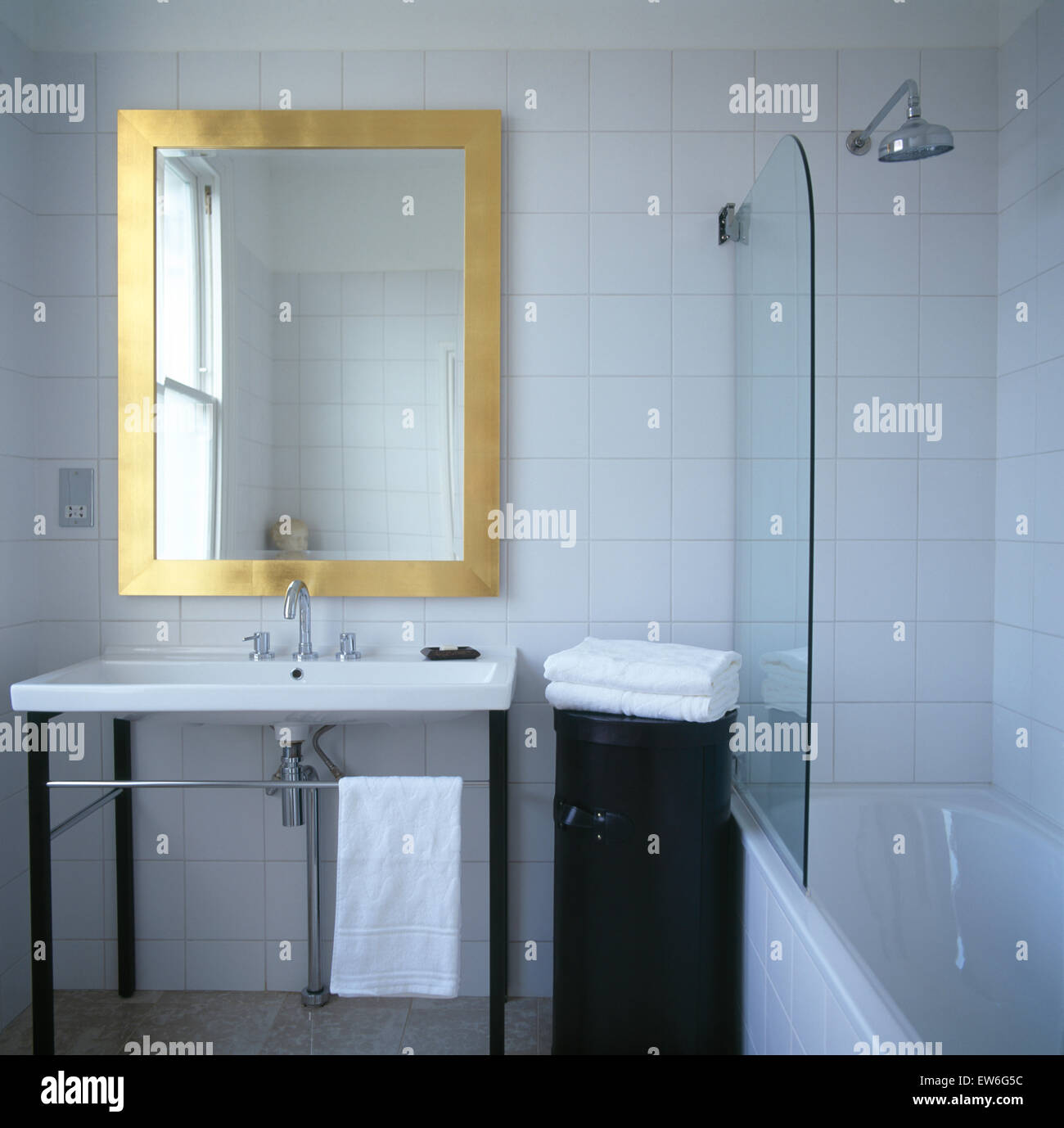 Brass framed mirror above washbasin in modern tiled bathroom with ...