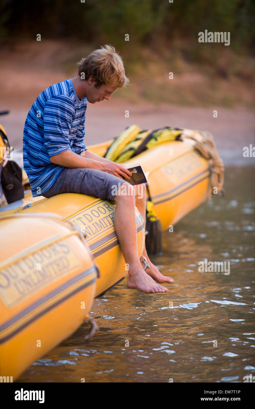 Man Reading A Book In Raft At The Rivers Edge Deep Canyon