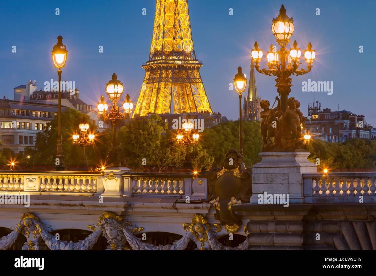 Twilight over lights of Pont Alexandre III with Eiffel Tower beyond, Paris, Ile-de-France, France - Stock Image
