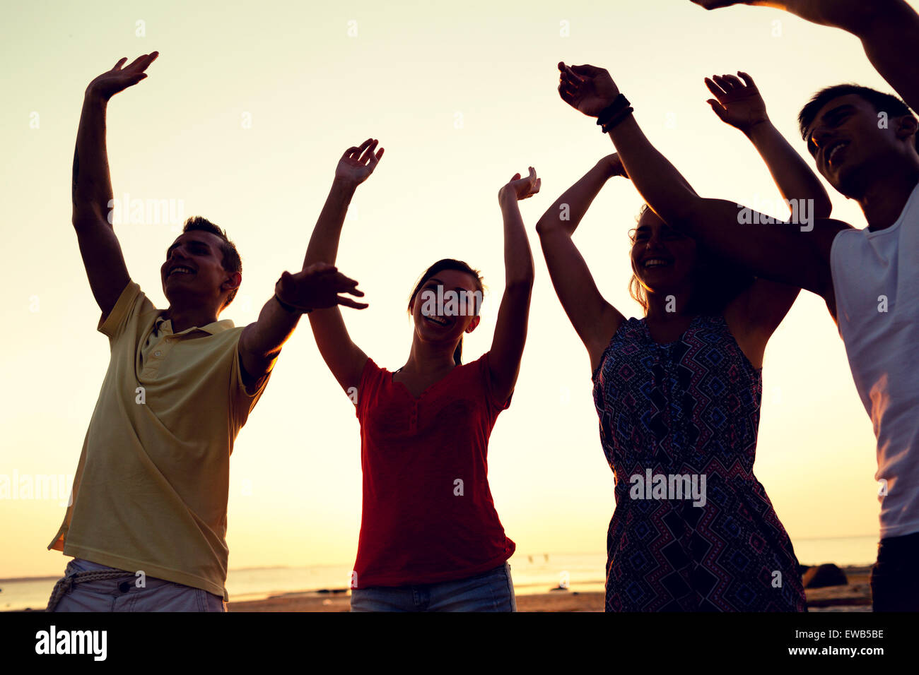 smiling friends dancing on summer beach - Stock Image