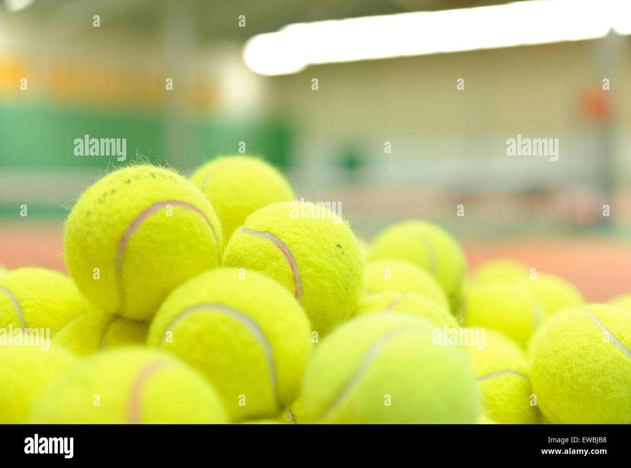 Pile of tennis balls in a basket - Stock Image