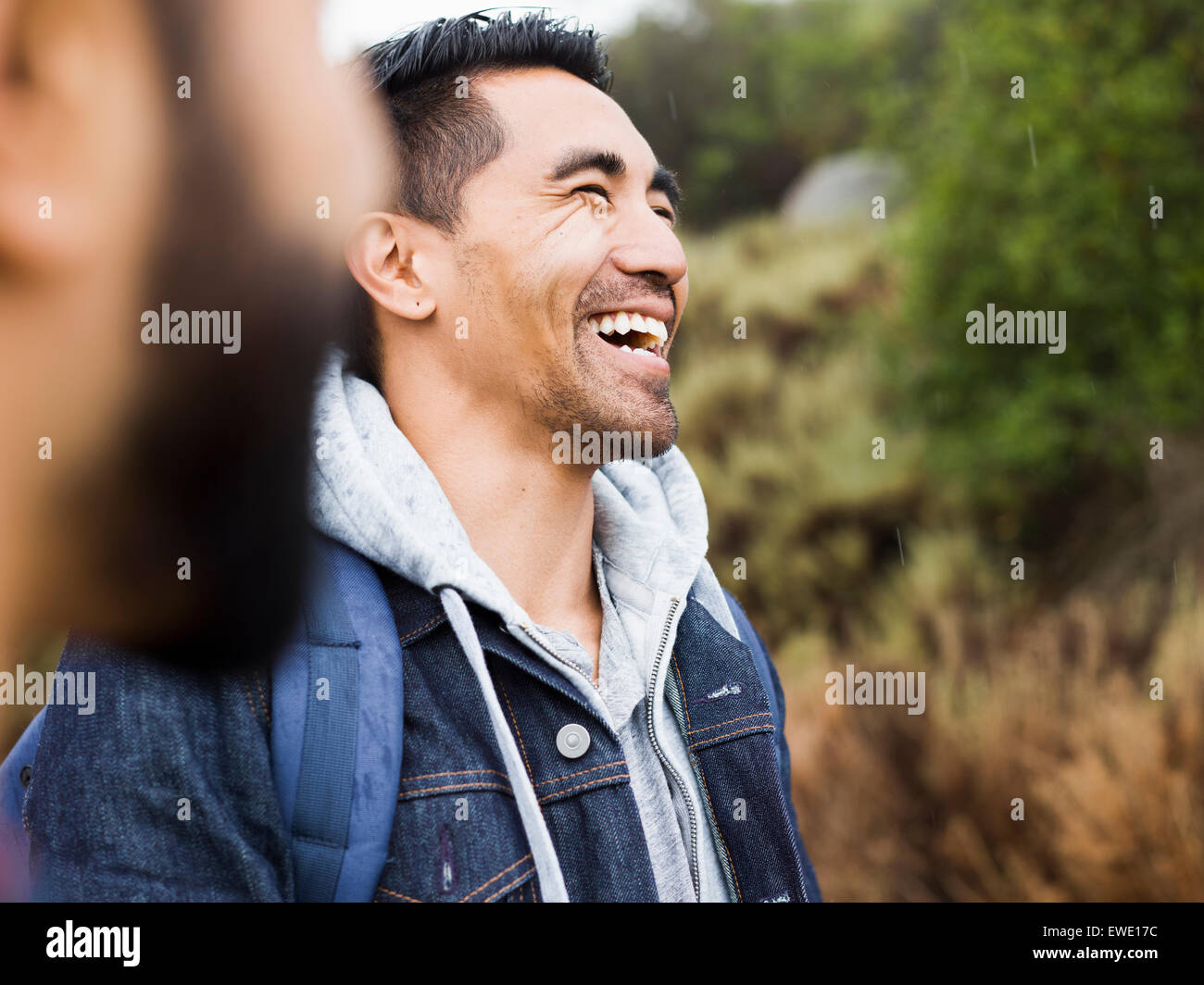 Two men, one laughing with his head back - Stock Image