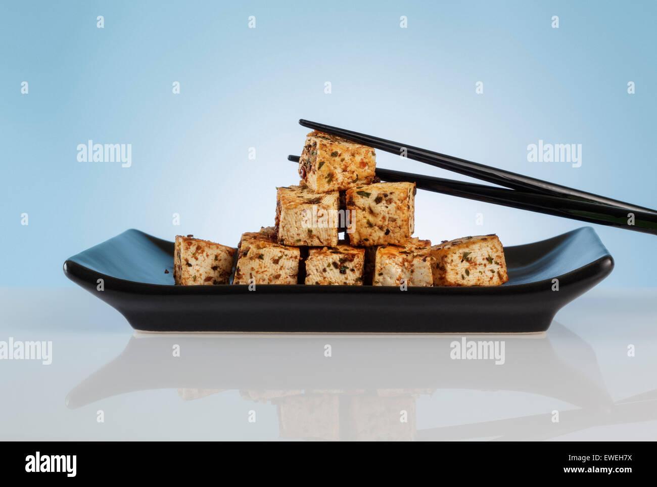 Spiced Tofu Cubes on black Dish - Stock Image