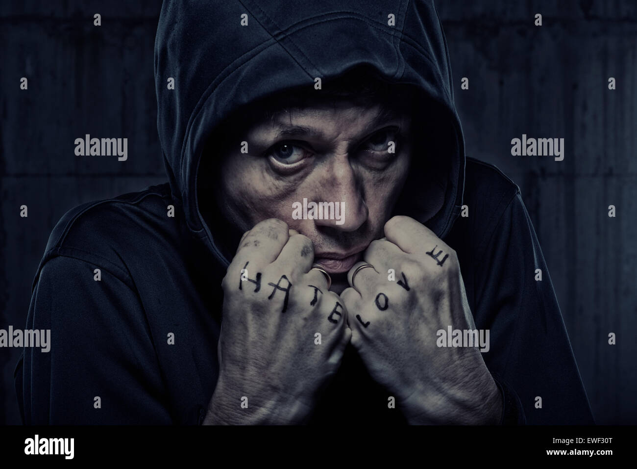 Grizzled man in hooded jacket with fists marked 'Hate' and 'Love' - Stock Image