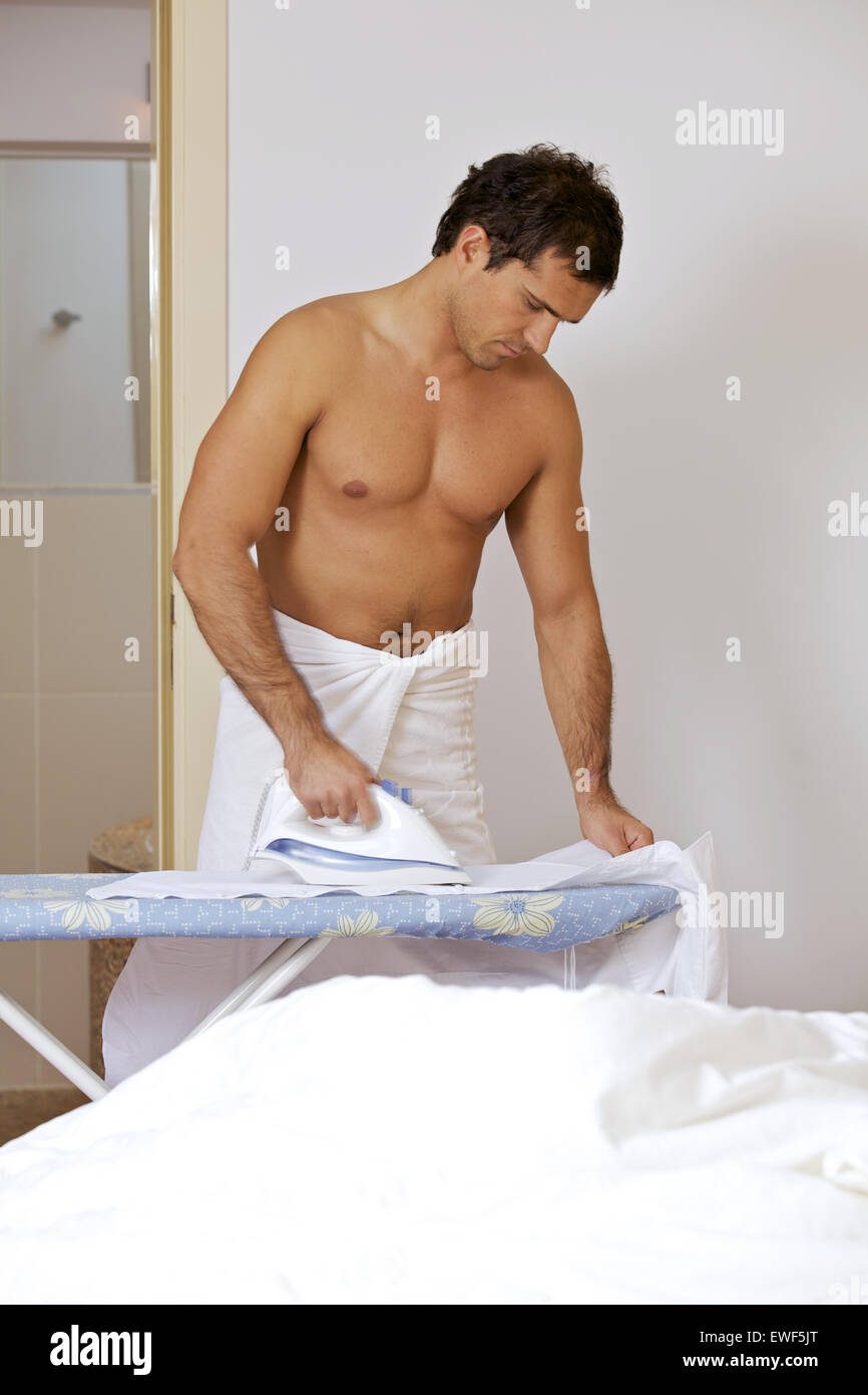 Man in towel ironing clothes on a stand - Stock Image
