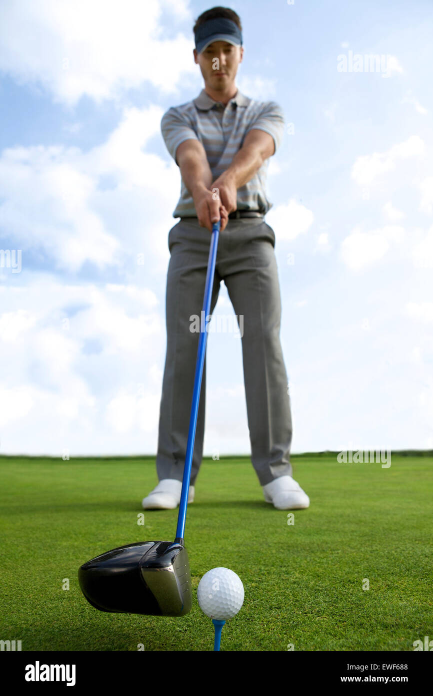 Man about to strike golf ball, low angle view - Stock Image