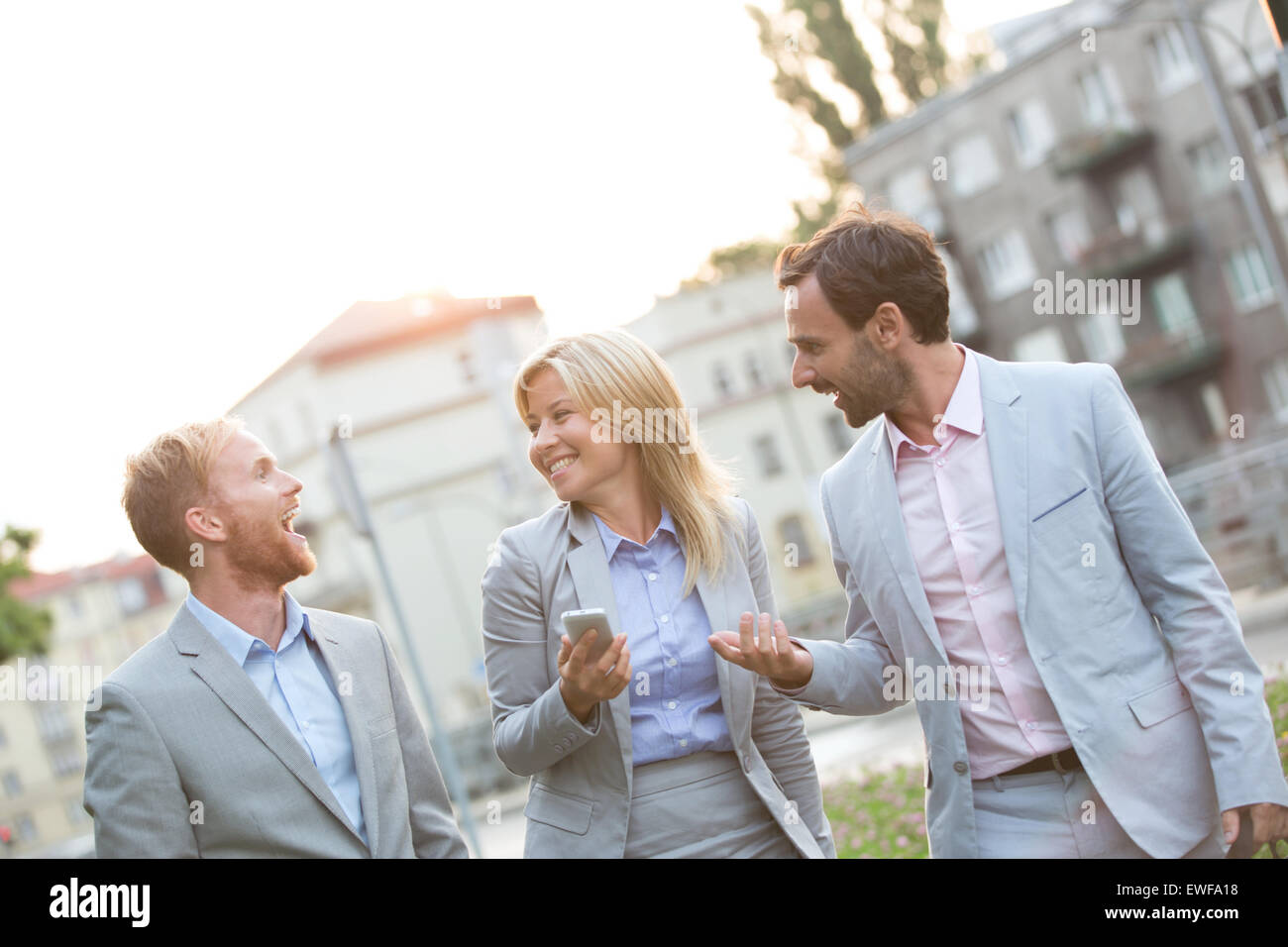 Cheerful businesspeople walking in city - Stock Image