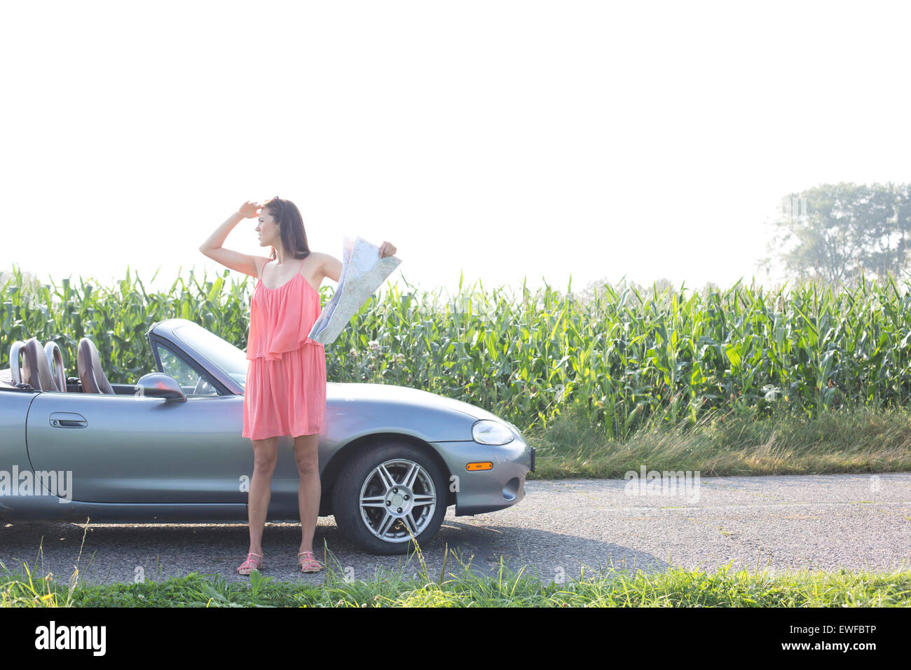 Full length of woman shielding eyes while holding map by convertible - Stock Image