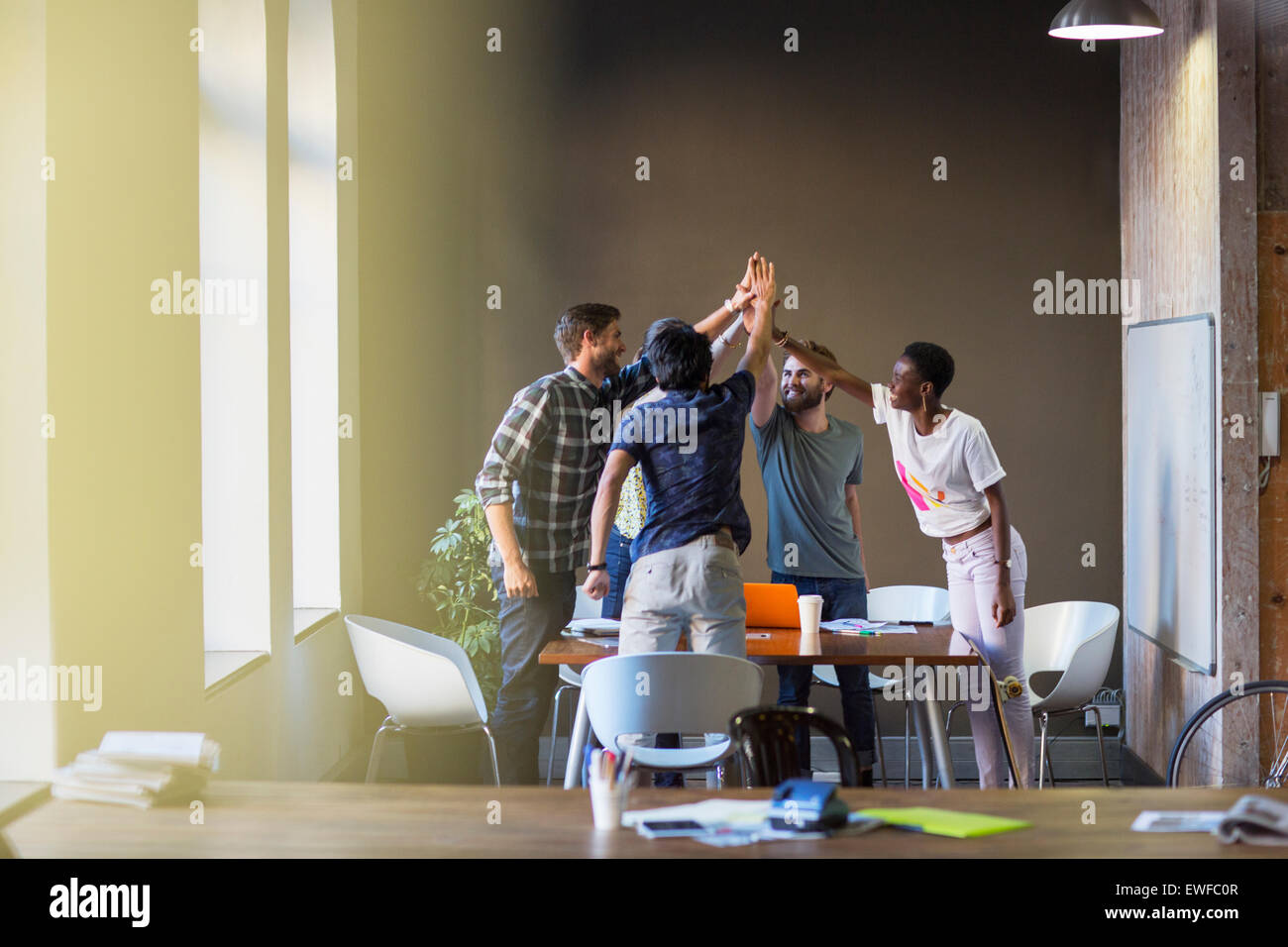 Creative business people joining hands at table in office - Stock Image