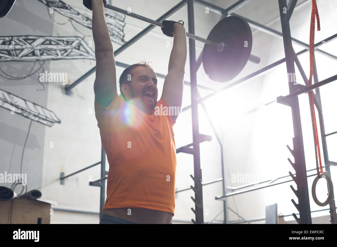 Dedicated man lifting barbell in crossfit gym - Stock Image