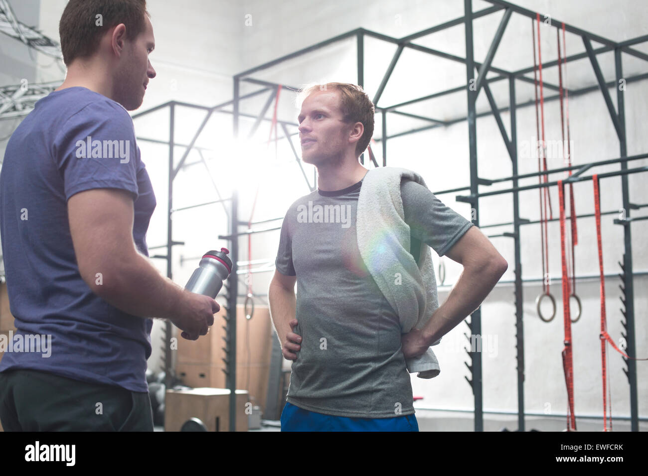 Male friends talking in crossfit gym Stock Photo
