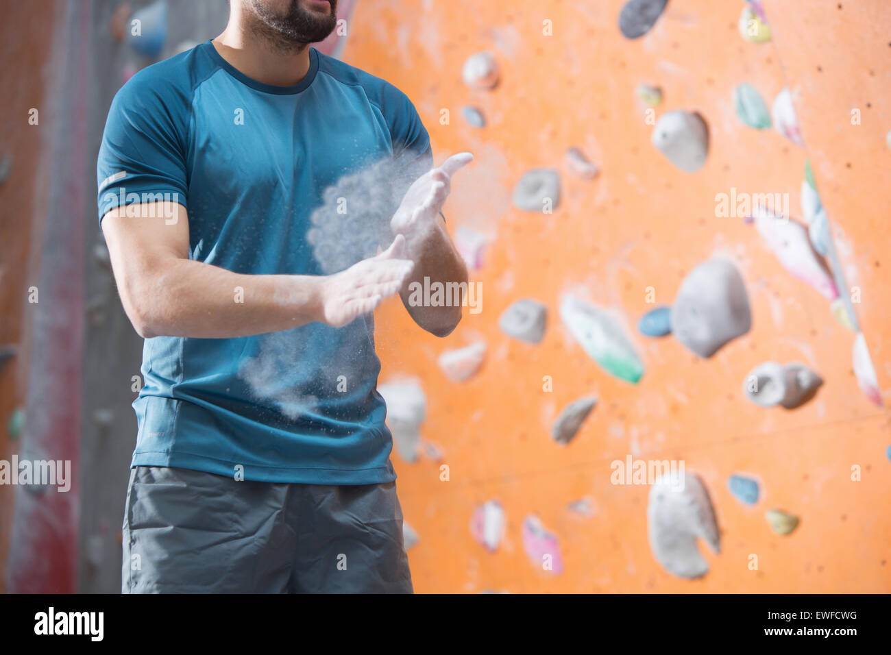 Midsection of man dusting powder by climbing wall in crossfit gym - Stock Image