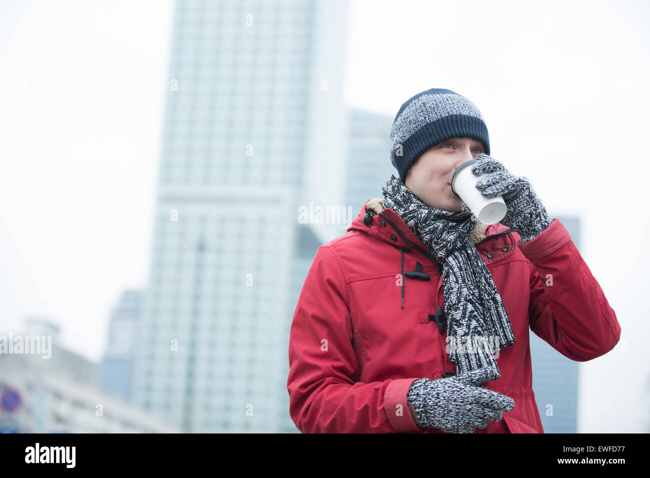 Man in warm clothing drinking coffee outdoors - Stock Image
