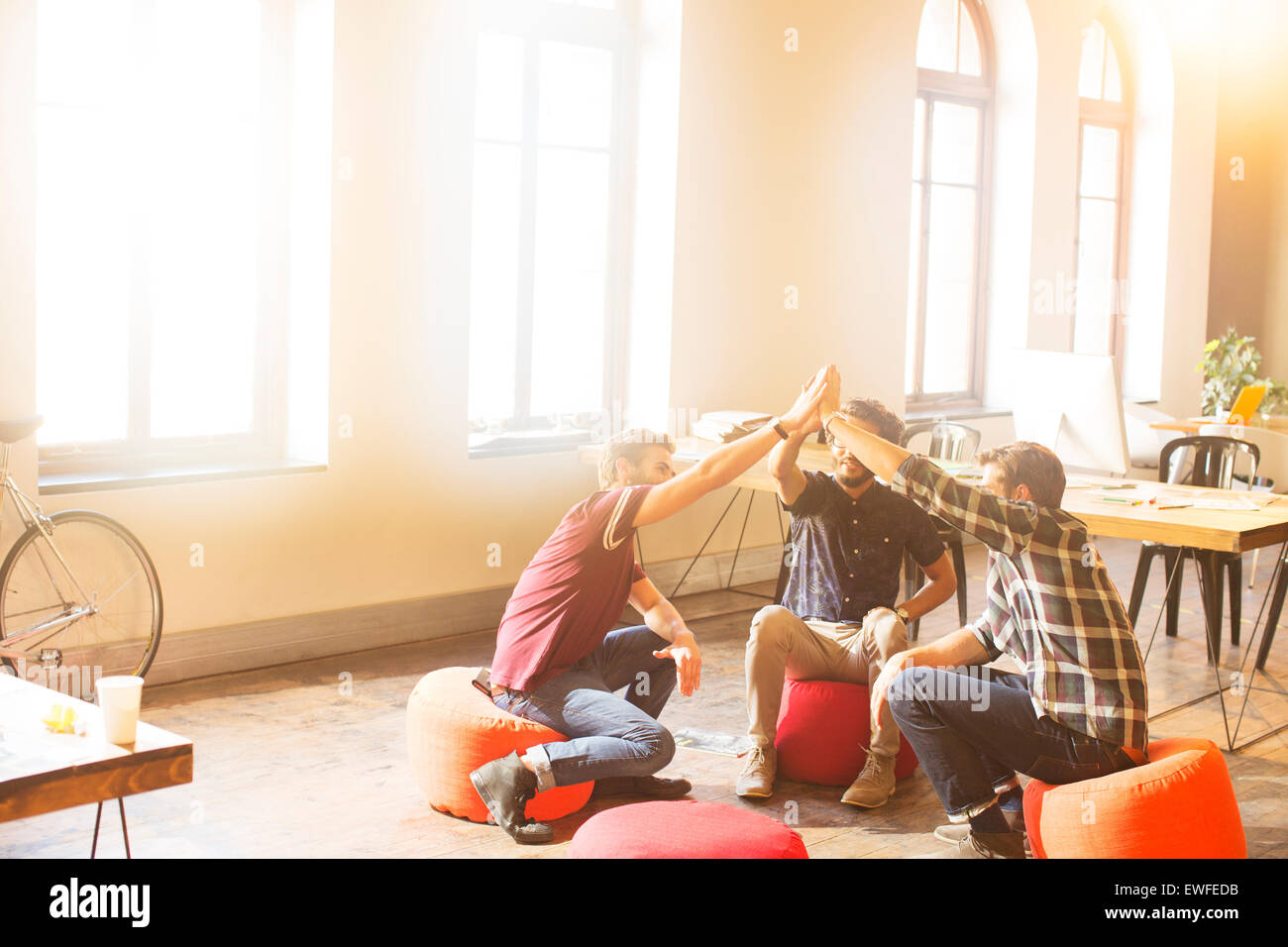 Creative business people joining hands in circle in sunny office - Stock Image