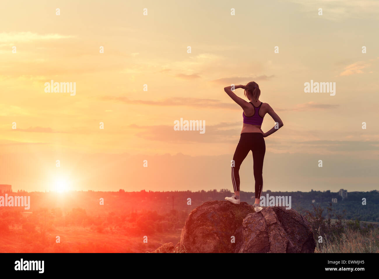 Young sporty woman with arms raised up at sunset in summer - Stock Image