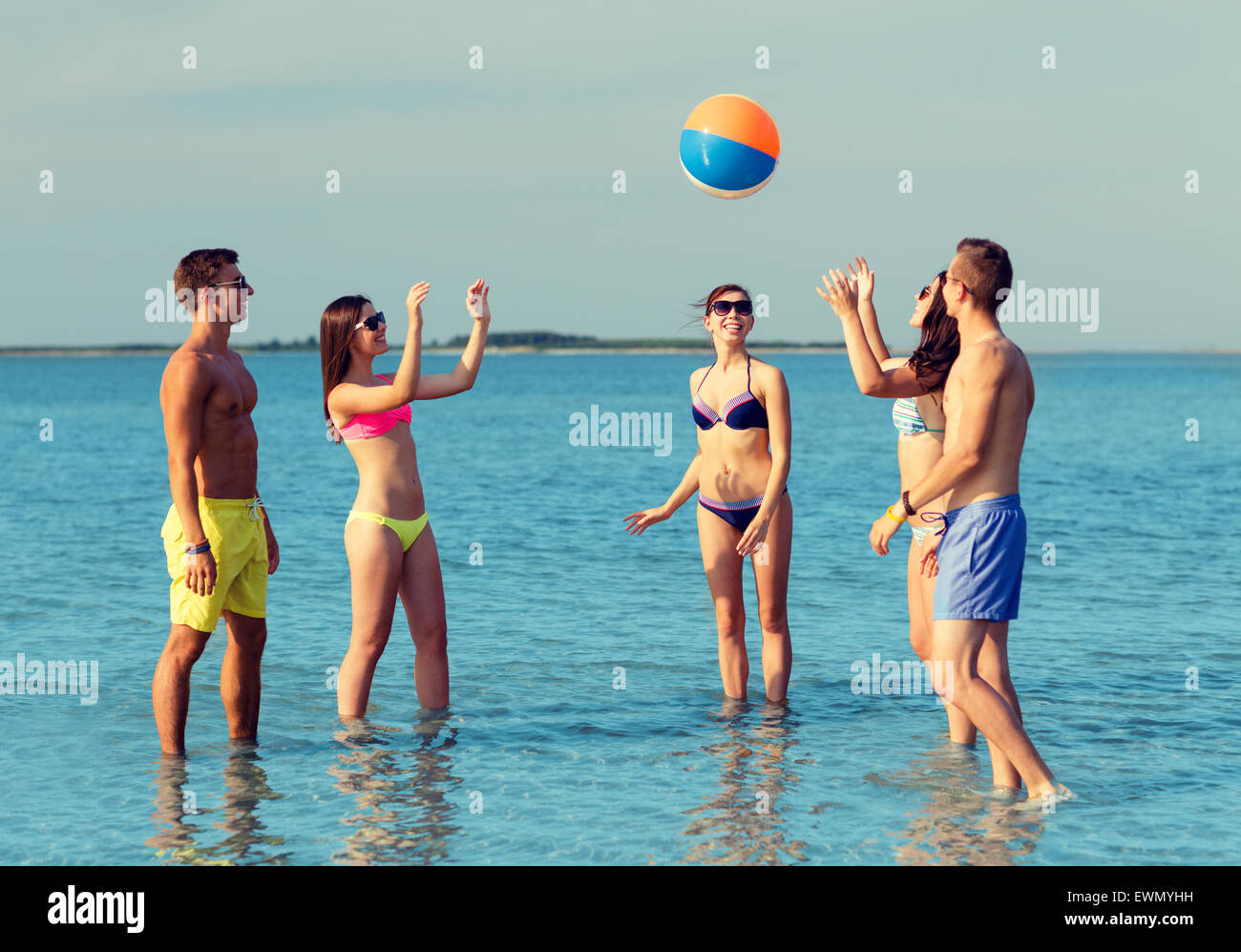 smiling friends in sunglasses on summer beach - Stock Image