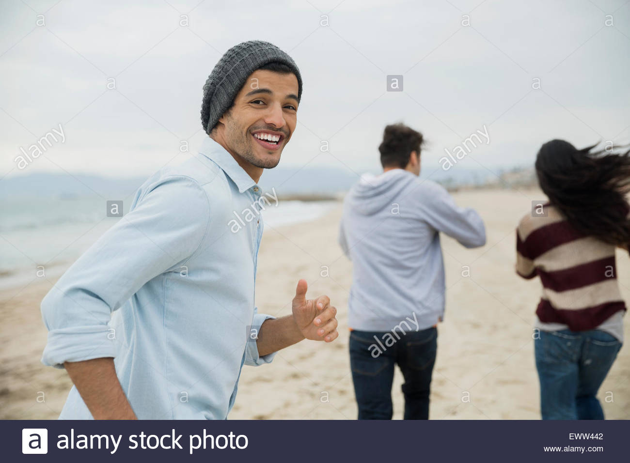 Portrait smiling man running with friends on beach - Stock Image