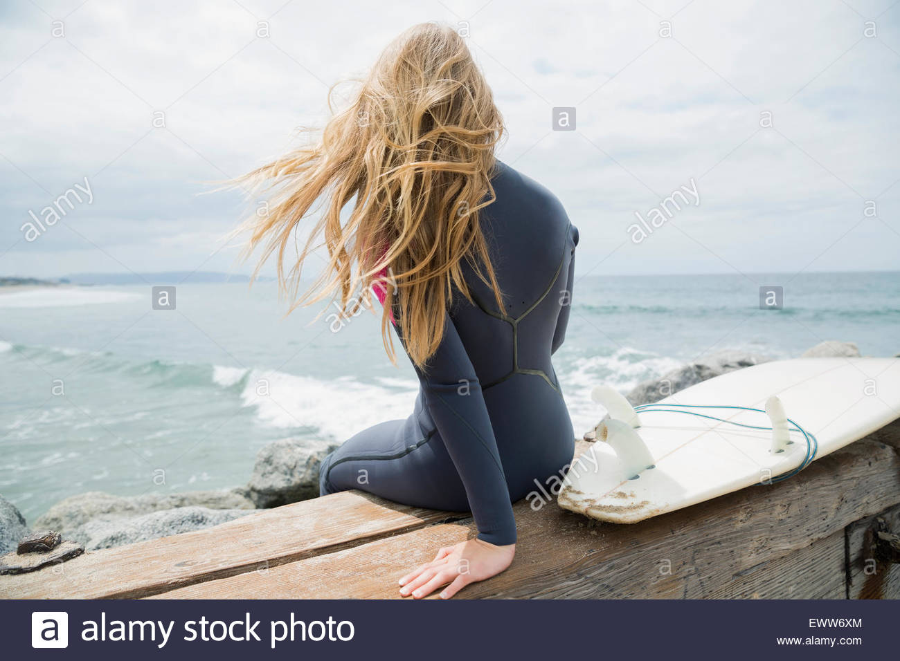 Blonde female surfer sitting with surfboard ocean jetty - Stock Image