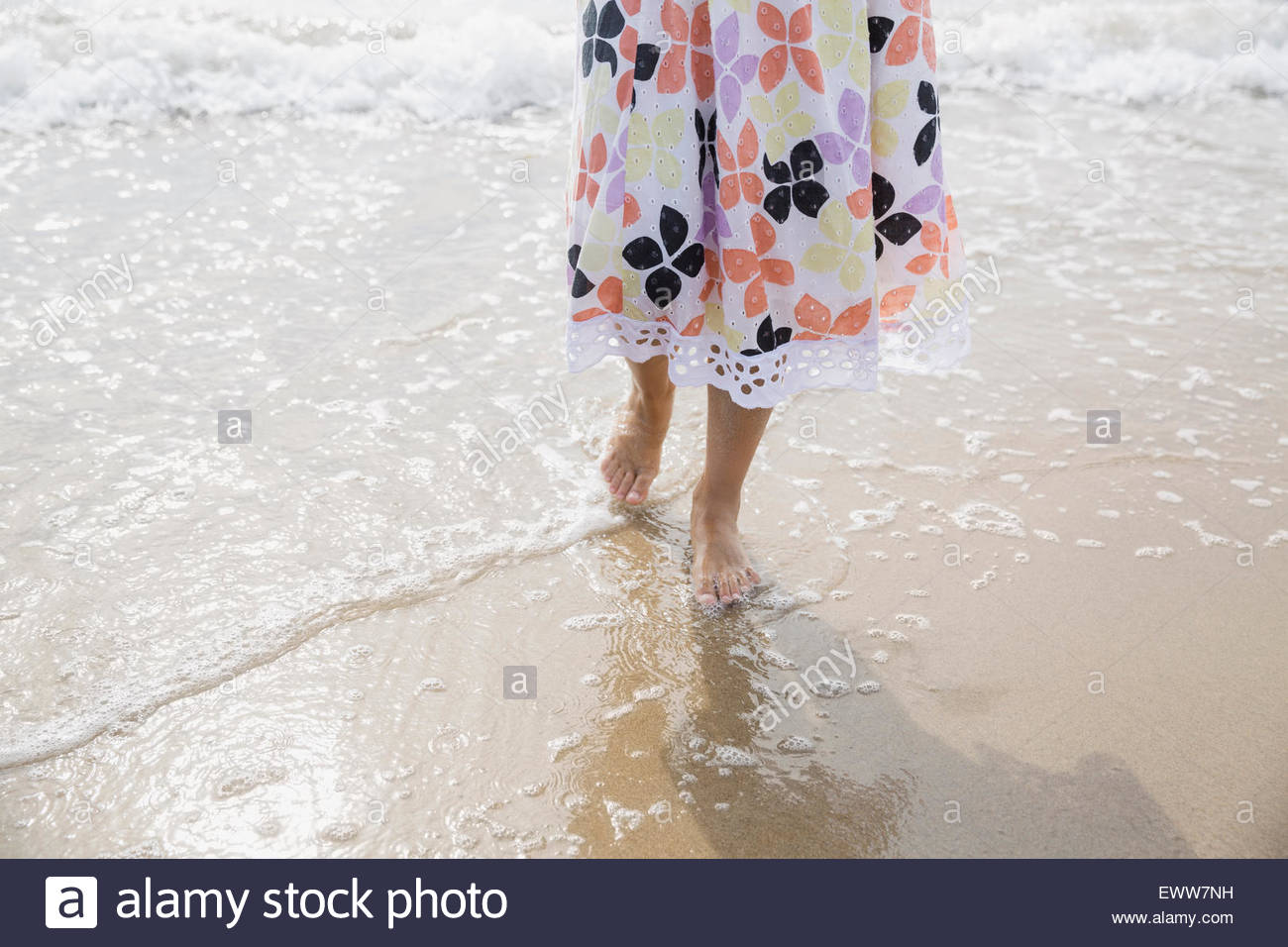Low section girl sun dress wading ocean surf - Stock Image