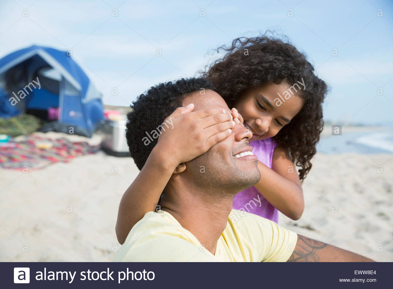 Daughter covering father eyes on beach - Stock Image